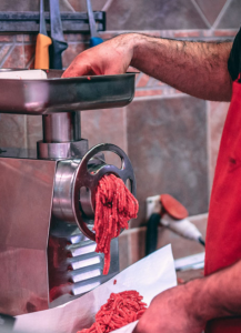 man using meat mincer